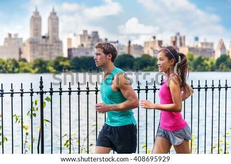 Running couple runners jogging in Central Park, NYC living healthy fitness lifestyle. People running summer training for marathon in Manhattan, New York. Asian female model and Caucasian male athlete. - stock photo