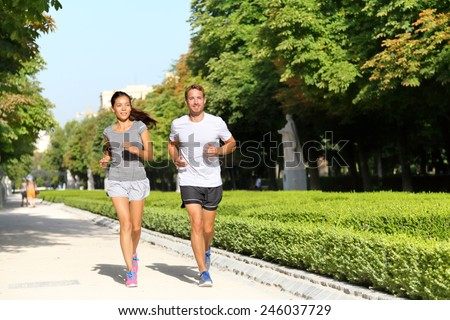 Running couple runners jogging in city park. Exercising woman and man runner training together on run living healthy active lifestyle in Buen Retiro Park, Parque el Retiro in Madrid, Spain, Europe. - stock photo