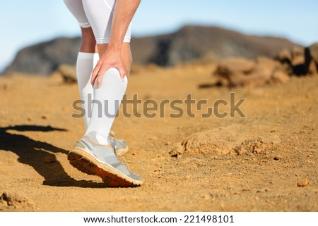 Running Cramps in leg calves or sprain calf on runner. Sports injury concept with running fitness man athlete outside. - stock photo