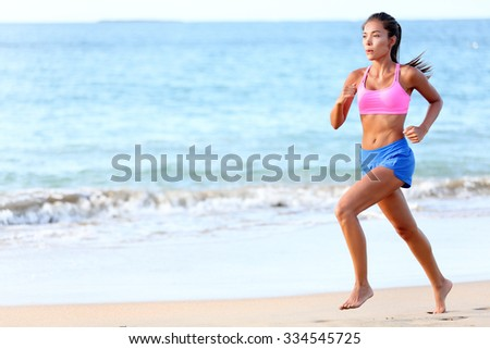 Running Determined young woman runner jogging on beach. Full length of fit female is in sports clothing. Jogger is exercising at sea shore during sunny day. - stock photo