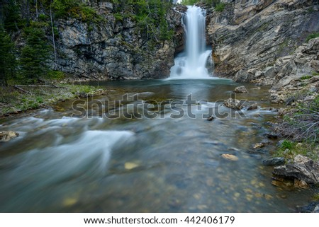 Running Eagle Falls - A spring evening view of Running Eagle Falls at Two Medicine Valley region of Glacier National Park, Montana, USA. - stock photo