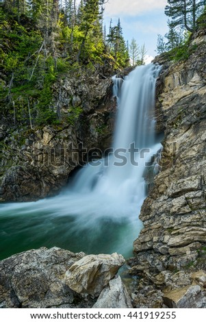 Running Eagle Falls - Vertical - A spring evening view of Running Eagle Falls at Two Medicine Valley region of Glacier National Park, Montana, USA. - stock photo
