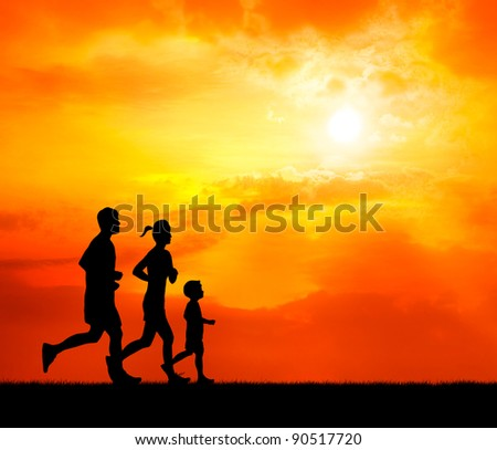 running family at sunset silhouetted - stock photo