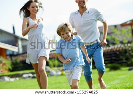 Running family on a lawn - stock photo
