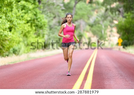 Running fit woman - female runner training outdoors jogging on red road in amazing landscape nature. Fit beautiful fitness model working out outside in summer. - stock photo