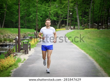 Running fitness man sprinting outdoors in beautiful park.  - stock photo