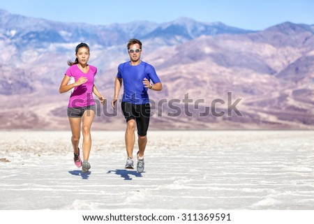 Running Fitness people. Full length of determined couple jogging against mountains. Young partners are in sports clothing. They are representing their healthy lifestyle. - stock photo