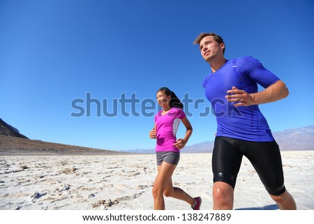 Running fitness sport runners in extreme run training in the desert. Athlete running multiracial running couple. Fit caucasian man sports model and sporty Asian woman exercising outdoors in summer. - stock photo