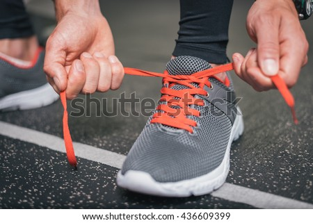 Running footwear close up. Gym indoor workout and fitness healthy concept. Male athlete tying sport shoes laces before training. - stock photo