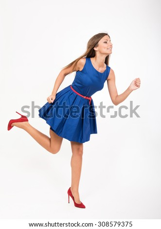 Running girl in blue dress, studio full length portrait - stock photo
