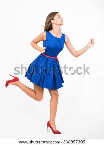 Running girl in blue dress, studio full length portrait