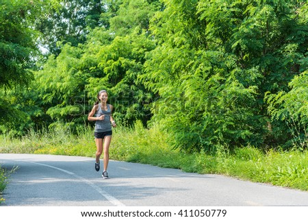 Running girl runner jogging on nature park path during summer training cardio for marathon race or weight loss goal success. Athlete Asian woman with fit body living a happy healthy lifestyle. - stock photo