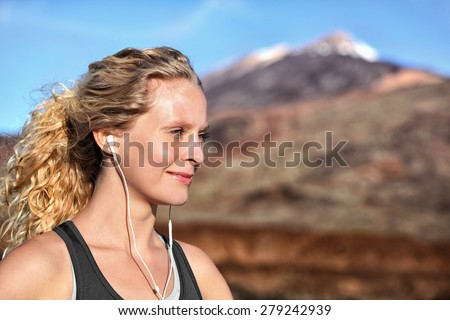 Running girl with earphones - woman runner listening to music in earbuds. Female athlete portrait after running in beautiful nature. Healthy lifestyle concept with beautiful young blonde fitness model - stock photo