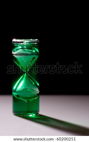 Running green crystal hourglass shot with backlight - stock photo