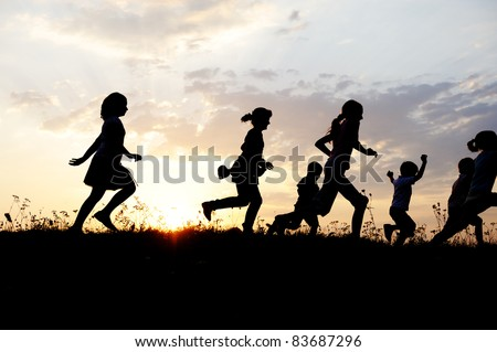Running group of children running on meadow, sunset, silhouette - stock photo