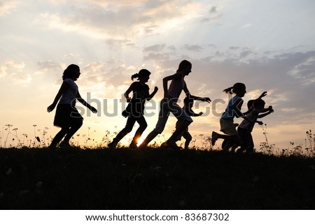 Running group of happy children playing on meadow, sunset, summertime