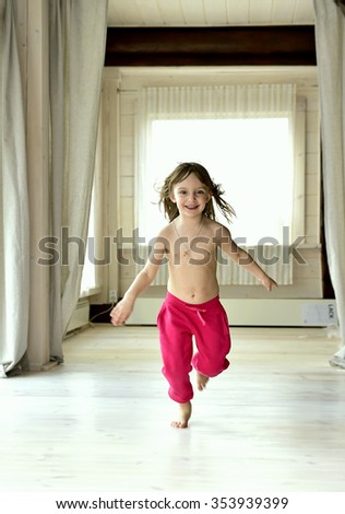 Running happy smiling little girl in red pants in the light room - stock photo