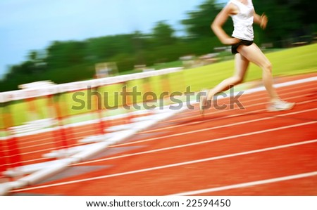 Running in a hurdle race (motion blur) - stock photo