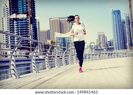 Running in city park. Woman runner outside jogging at morning with Dubai urban scene in background - stock photo
