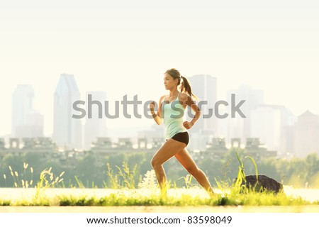 Running in city park. Woman runner outside jogging with Montreal skyline in background - stock photo
