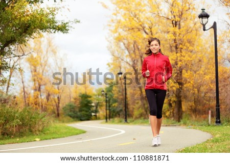 Running in Fall. Runner woman jogging in autumn forest. Beautiful young fit fitness sport model jogging with slight motion blur. Mixed race Caucasian / Asian girl. - stock photo