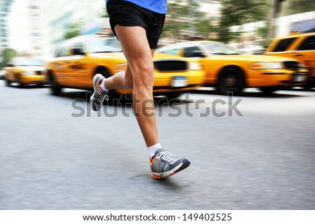 Running in New York City - man city runner jogging in street of Manhattan with yellow taxi caps cars and traffic. Urban lifestyle image of male jogger training downtown. Legs and running shoes. - stock photo