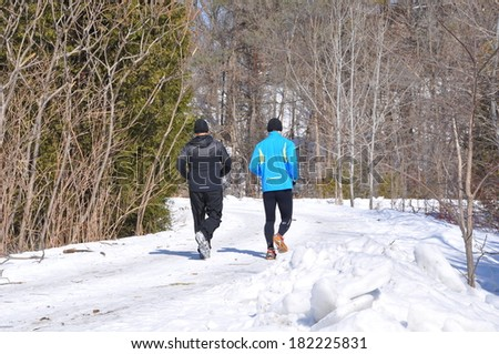Running in snow covered road - stock photo