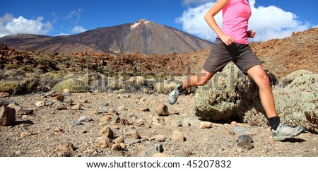 Running in spectacular volcano landscape on Teide, Tenerife. Woman in pink top. - stock photo