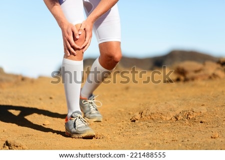Running injury - Male runner with knee pain. Trail runner injured jogging in nature clutching his knee in pain. Man fitness athlete.