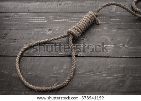 Running knot.Loop hempen rope on a dark wood tables background.  - stock photo
