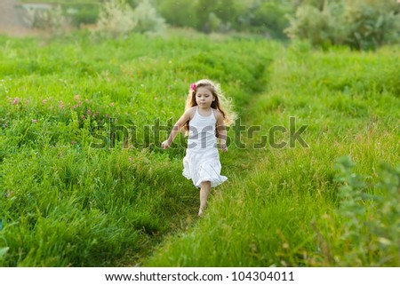 running  little happy girl running on green meadow field - stock photo