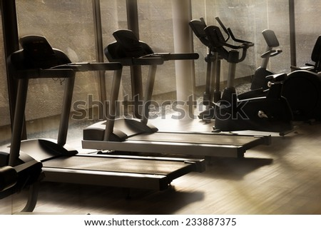 Running machines in fitness center with morning light. - stock photo