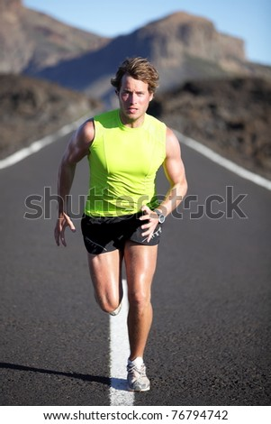 Running man athlete on road outdoors. Fit fitness runner man running and sweating in beautiful rough landscape. Full body image of young muscular Caucasian man. - stock photo