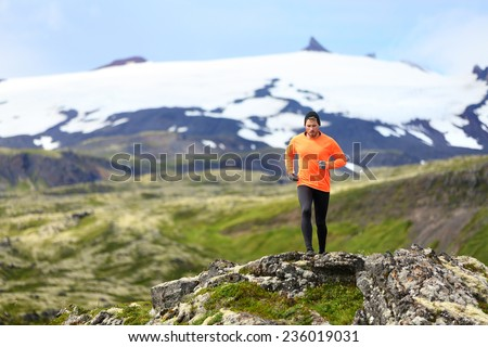 Running man exercising - trail runner athlete. Fit male sport fitness model training and jogging outdoors living healthy lifestyle in beautiful mountain nature, Snaefellsjokull, Snaefellsnes, Iceland. - stock photo
