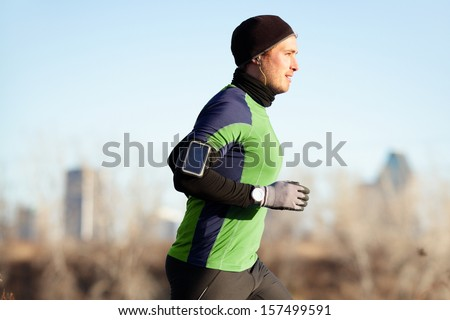 Running man jogging in autumn listening to music on smart phone. Runner training in warm outfit on cold day. Fit male fitness athlete model training outdoor in fall. Full body length of jogger. - stock photo