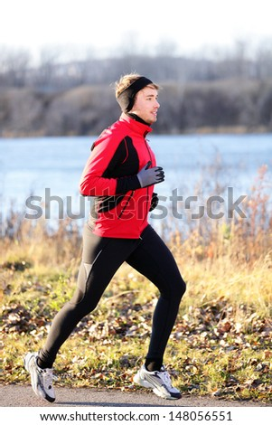 Running man jogging in autumn outdoor on cold day wearing long tights and sporty jogging outfit. Fit male fitness athlete model training outdoor in fall. Full body length of jogger. - stock photo