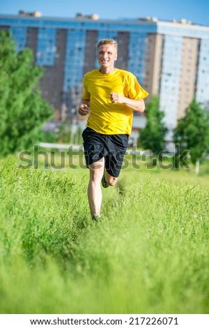 Running man jogging in city street park at beautiful summer day. Sport fitness model caucasian ethnicity training outdoor. - stock photo