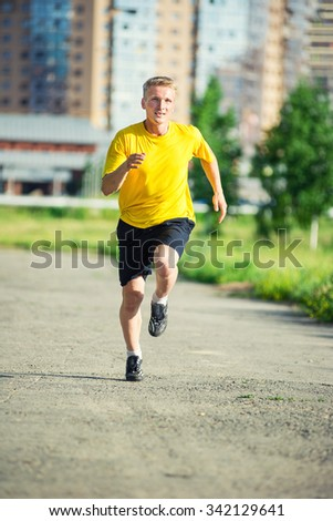 Running man jogging in city street park at beautiful summer day. Sport fitness model caucasian ethnicity training outdoor. - stock photo
