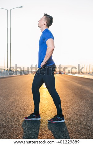 Running man. Male runner at sprinting speed training for marathon outdoors in amazing sunset on highway. Strong and fit caucasian male fitness model.