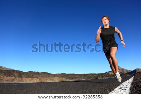 Running man. Male runner at sprinting speed training for marathon outdoors in amazing volcanic desert landscape. Strong and fit caucasian male fitness model.