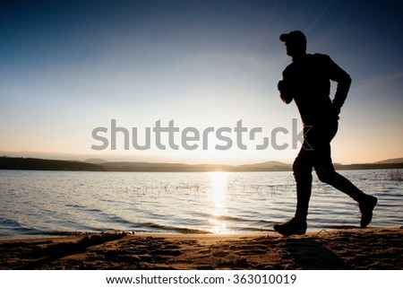 Running man on beach. Sportsman run in baseball cap, jogging guy during the sunrise above sandy beach - stock photo