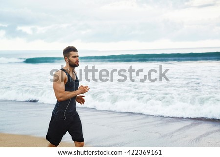 Running Man. Sporty Runner Enjoying Run By Sea During Outdoor Workout. Handsome Fit Athletic Male Jogging On Beach. Healthy Active Jogger Exercising And Training For Marathon. Fitness, Sports Concept - stock photo