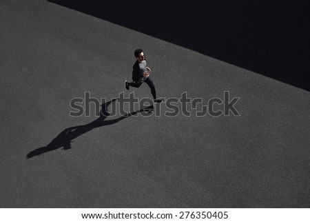 Running man sprinting for success on run. Top view athlete runner training at fast speed at black asphalt. Muscular fit sport model sprinter exercising sprint in yellow sportswear.  - stock photo
