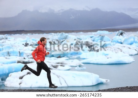 Running man. Sprinting trail runner in fast sprint in beautiful nature landscape. Fit male athlete sprinter cross country running by icebergs in Jokulsarlon glacial lake in Iceland. - stock photo
