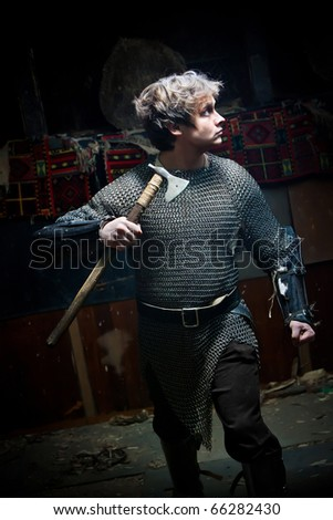 Running medieval warrior in the chain armour with the axe - stock photo