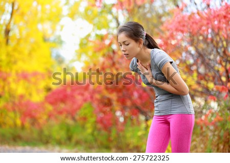 Running nausea - nauseous and sick ill runner vomiting. Running woman feeling bad about to throw up. Girl having nausea from dehydration or chest pain. - stock photo