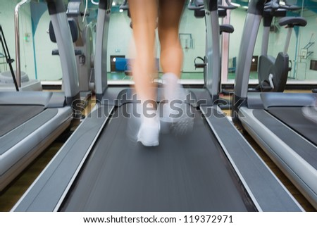 Running on a treadmill in the gym - stock photo