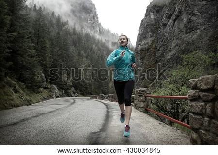 Running on the road around mountains under snowly rain. - stock photo