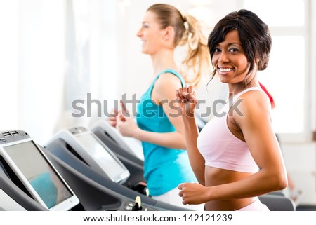 Running on treadmill in gym or fitness club - two women exercising to gain more fitness - stock photo