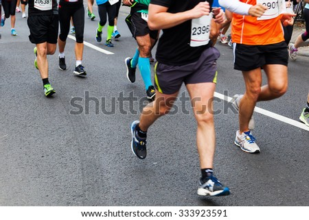 running people at a street marathon in slightly motion blur  - stock photo